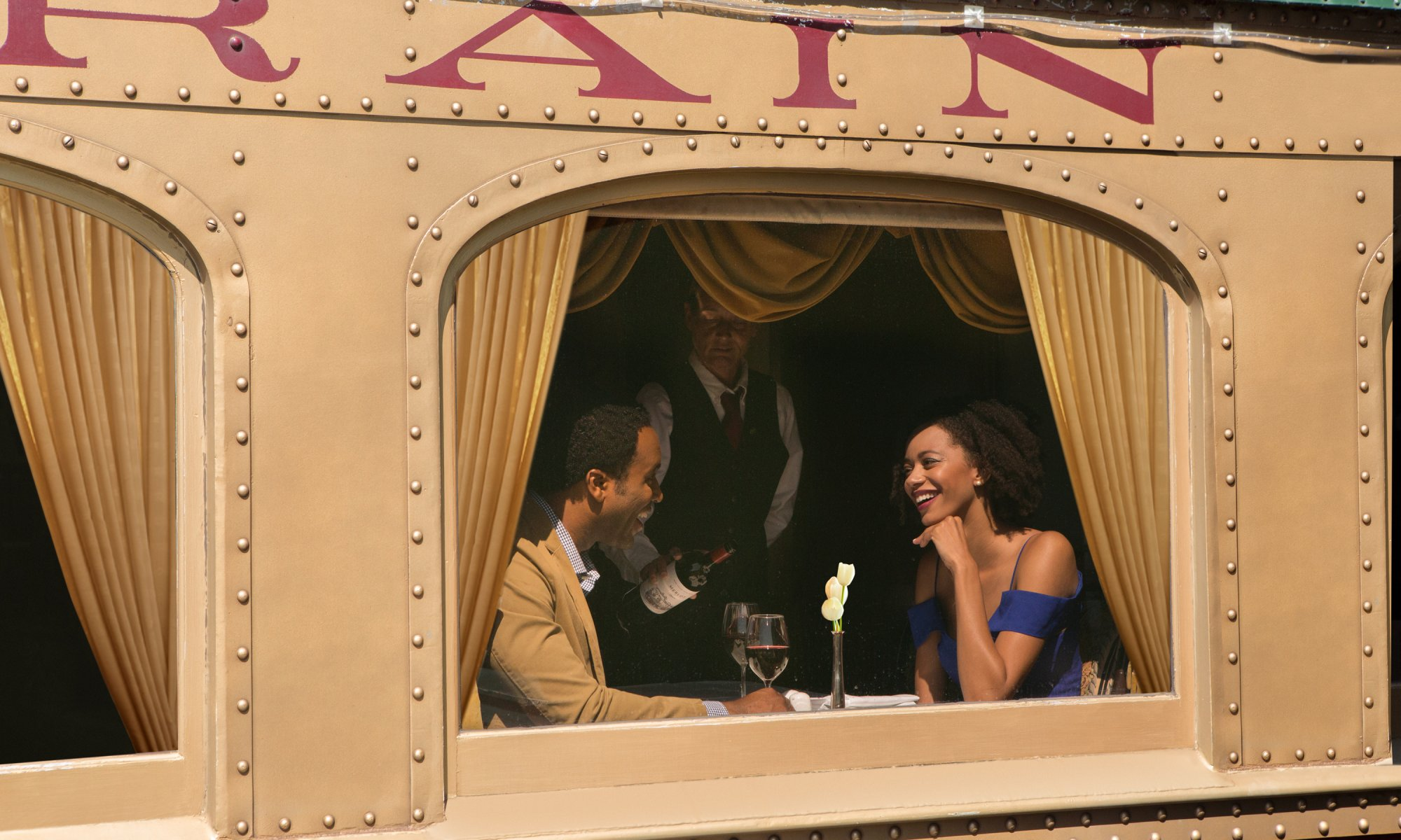Couple talking and sitting at table on Napa Valley Wine Train while server pours red wine into glasses
