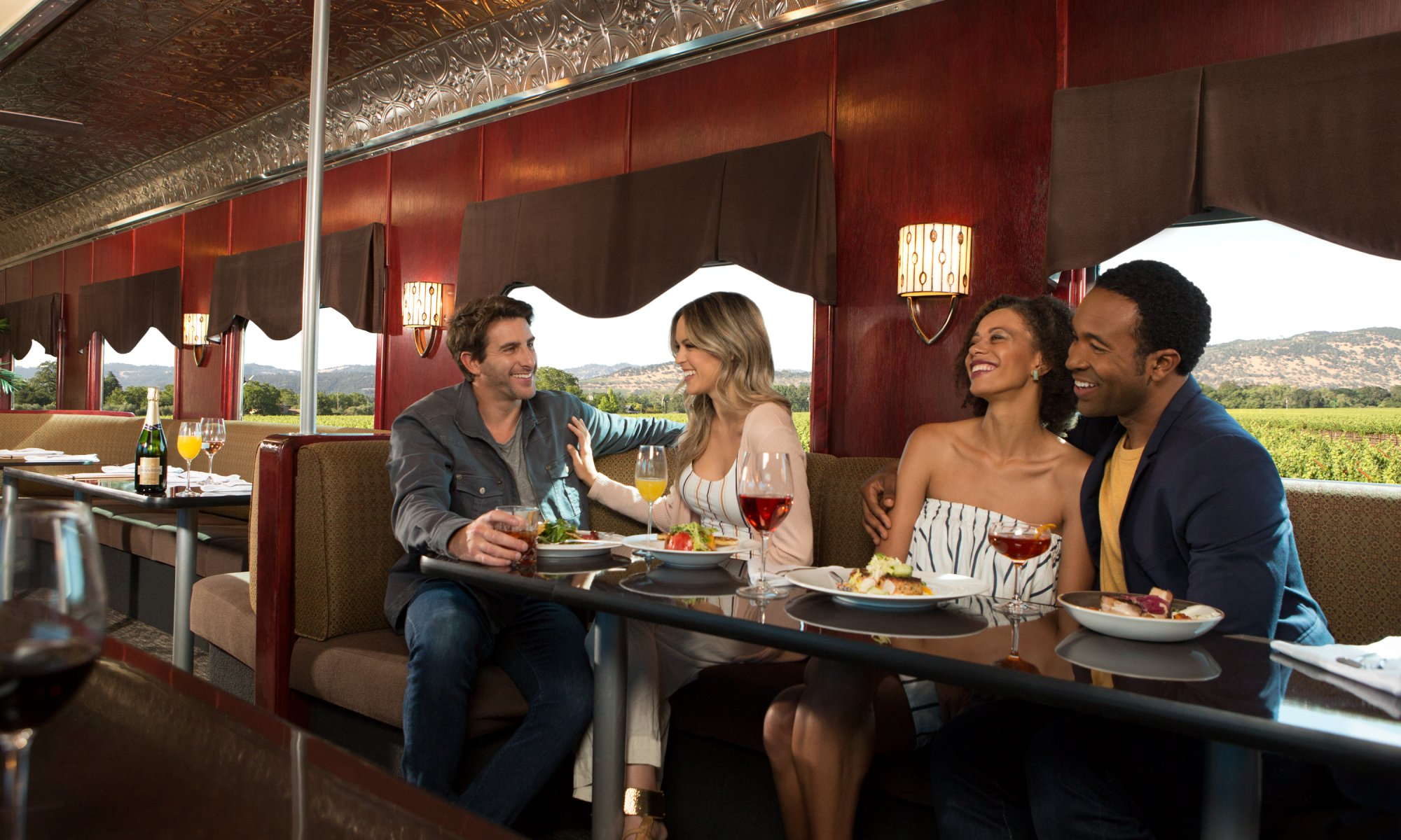 4 people enjoying a meal and glass of wine aboard the Napa Valley Wine Train