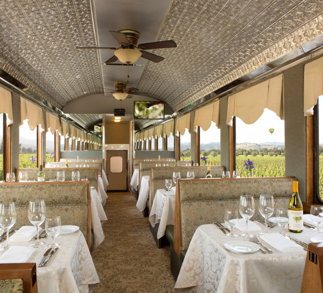 Pristine table settings and beige interior of Tower Railcar on Napa Valley Wine Train