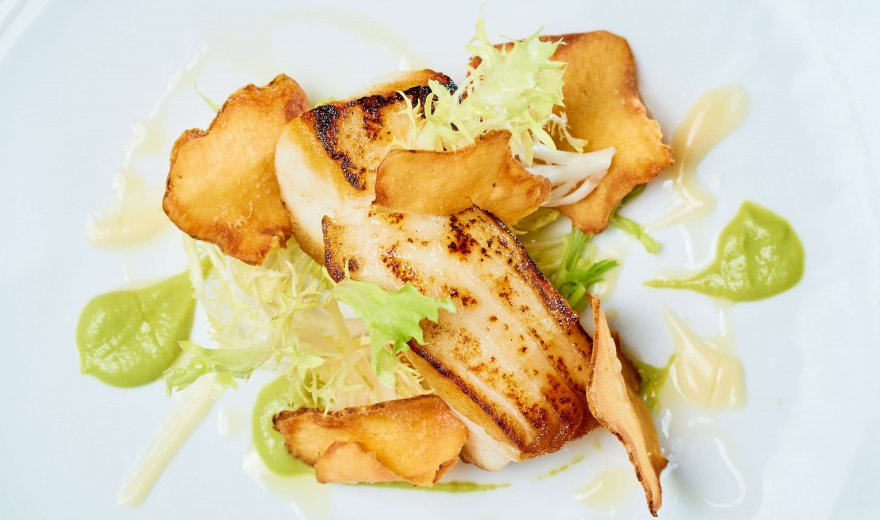 Close up of white plate with grilled white fish, deep fried handmade potato chips, light green lettuce, a green sauce, and some oil drizzled