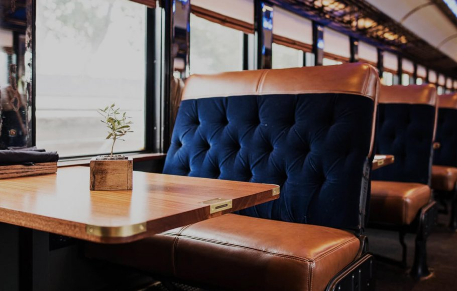 shot of empty table on Napa Valley Wine Train car with plush blue velvet and brown leather seats