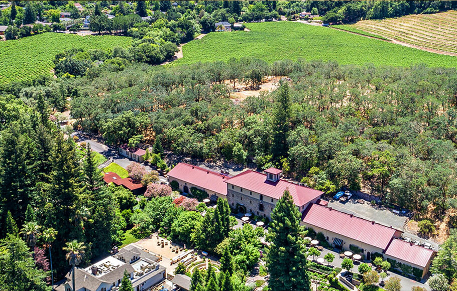 overhead view of Napa Valley winery with buildings with red tin roofs surrounded by trees