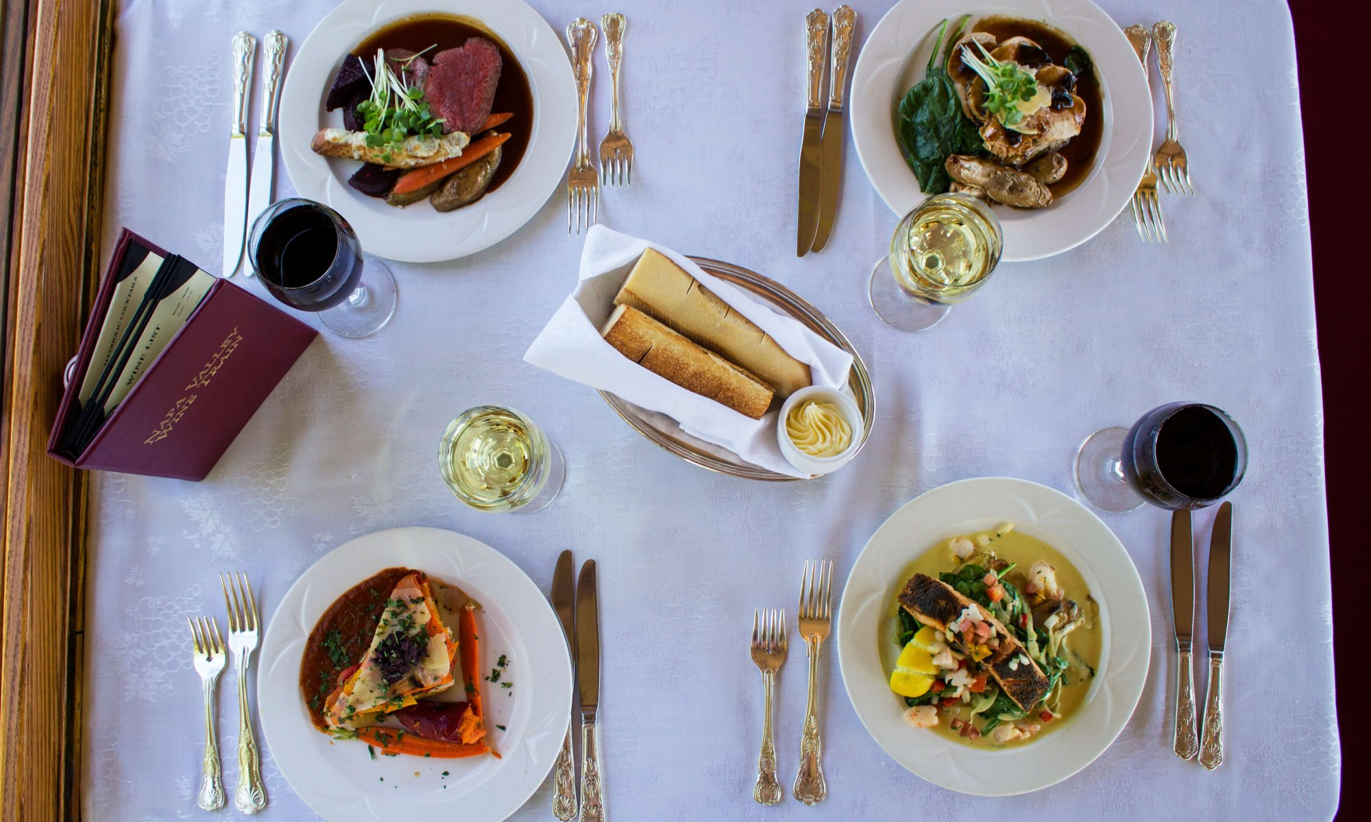 overhead shot of dinner table for four on the Napa Valley Wine Train featuring gourmet dishes, wine, and bread
