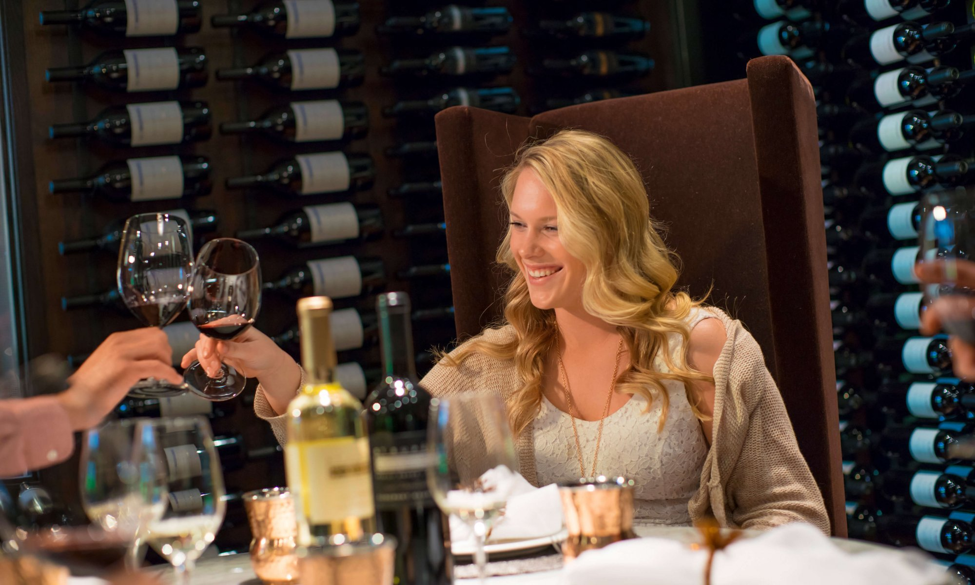 blonde woman sitting at table with a bottle of red and white wine clinking glasses with another guest