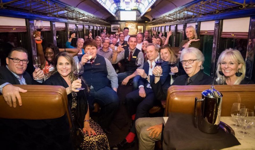 two dozen guests on Napa Valley Wine Train sitting and holding their glasses of wine up to cheers