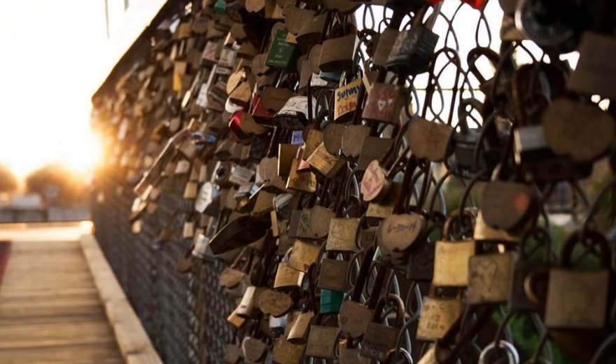 metal fence on a boardwalk-style bridge with hundreds of of locks signed with dates and names