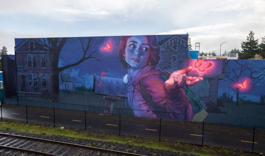 mural beside a railway featuring a woman, house, leafless tree, and glowing pink neon butterflies