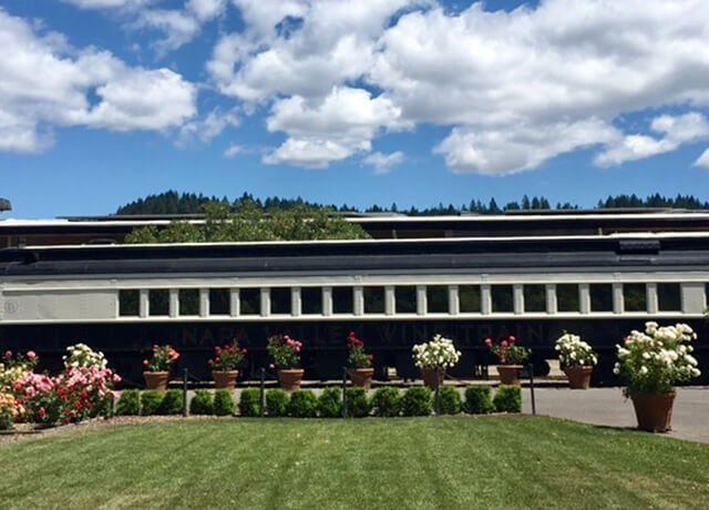 exterior shot of Napa Valley Wine Train with blue sky and white and pink flowers in front of train car