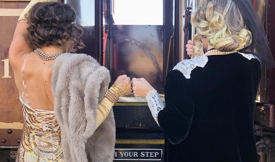 Two women with vintage costumes on facing the Napa Valley Wine Train