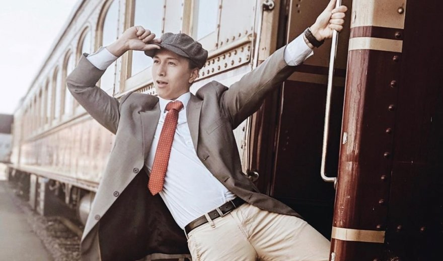Man in vintage suit and hat hanging off the side of the Napa Valley Wine Train