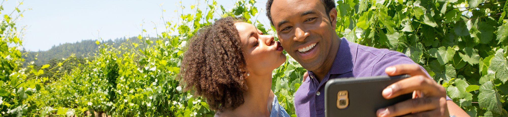 A couple takes a selfie on a cell phone in lush green vineyard in Napa Valley