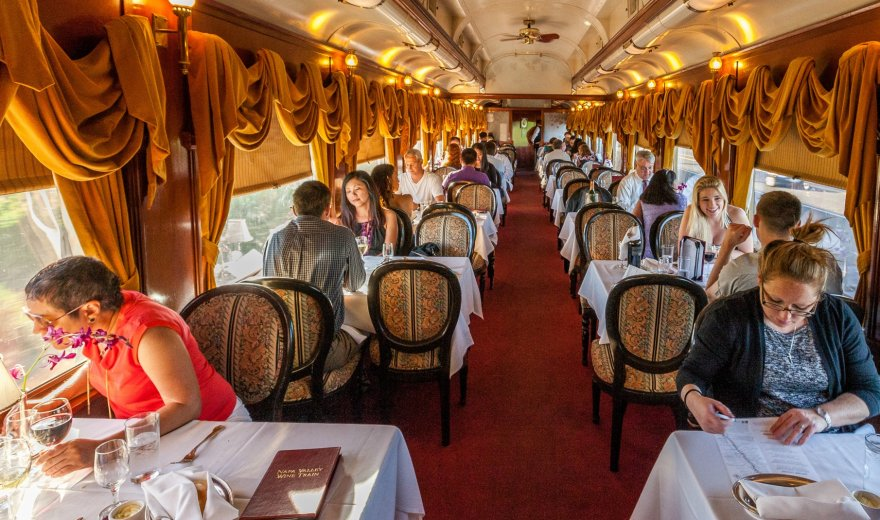 People sitting at tables aboard the Napa Valley Wine Train, red carpets and gold swagged curtains
