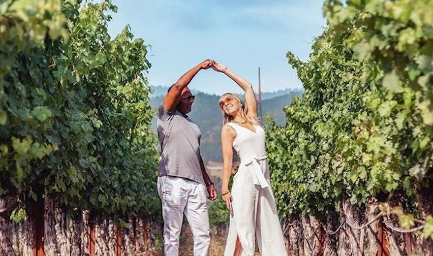 couple in vineyard hold hands