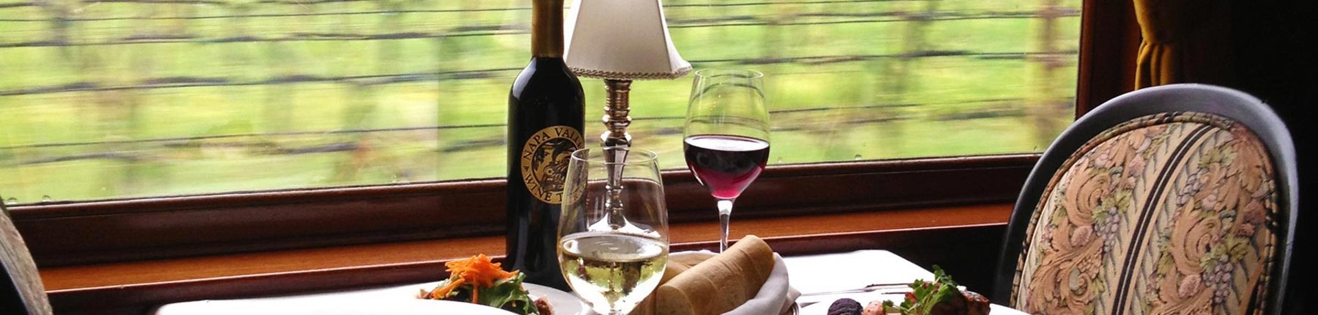 table set for dinner for two aboard Napa Valley Wine Train travelling through vineyard