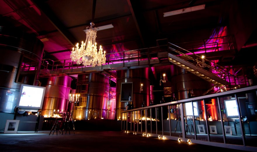 modern, dimly-lit winery with pink and yellow lights, steel bars, and chandelier hanging from the ceiling