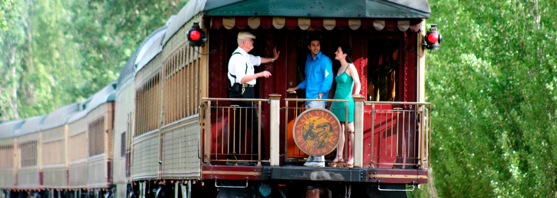 man and woman listening to conductor speak standing on back deck of Napa Valley Wine Train
