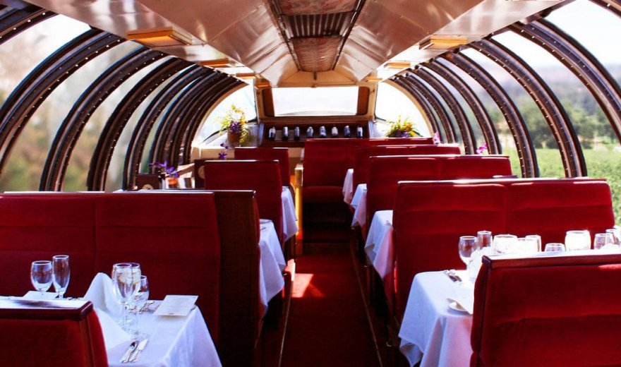 Photo of champagne vista dome train car which has floor to ceiling windows, velvet red seats, white table cloths on tables, a wine and champagne glass at each seat, and purple orchids on the tables. Outside the traincar is lush green vineyards.
