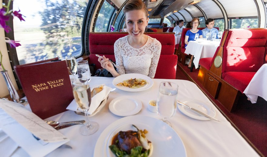 A woman sitting in plush red seat enjoying a meal in the Vista Dome Car on the Napa Valley Wine Train