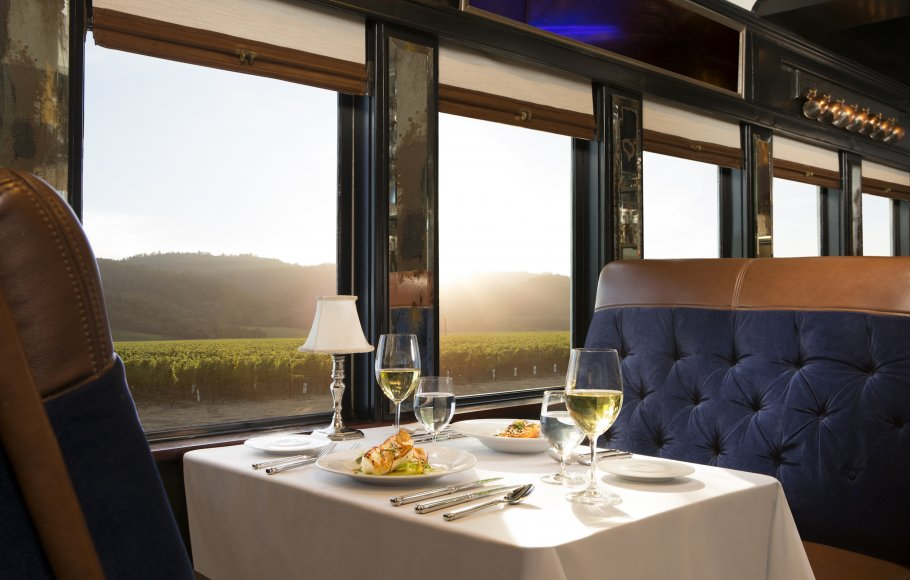 table with dinner for two on Napa Valley Wine Train with white wine, white fish dinner overlooking vineyards