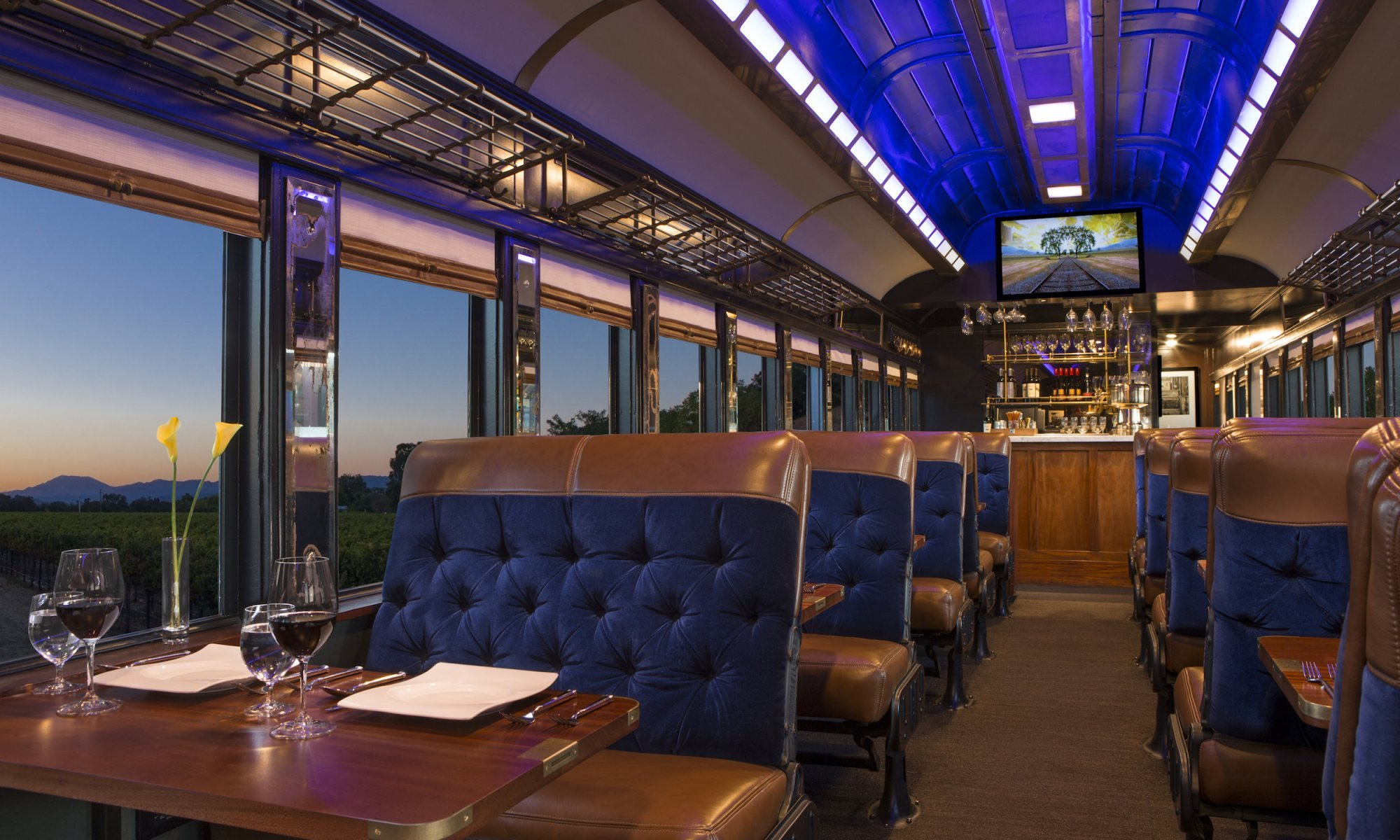 shot of Napa Valley Wine Train seating with plush blue velvet seats and glasses on red wine on the table