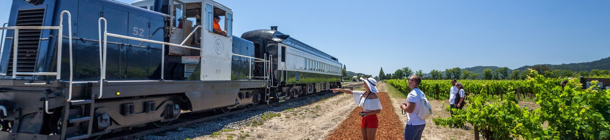 Woman pointing at exterior of Napa Valley Wine Train parked beside vineyard with blue sky overtop
