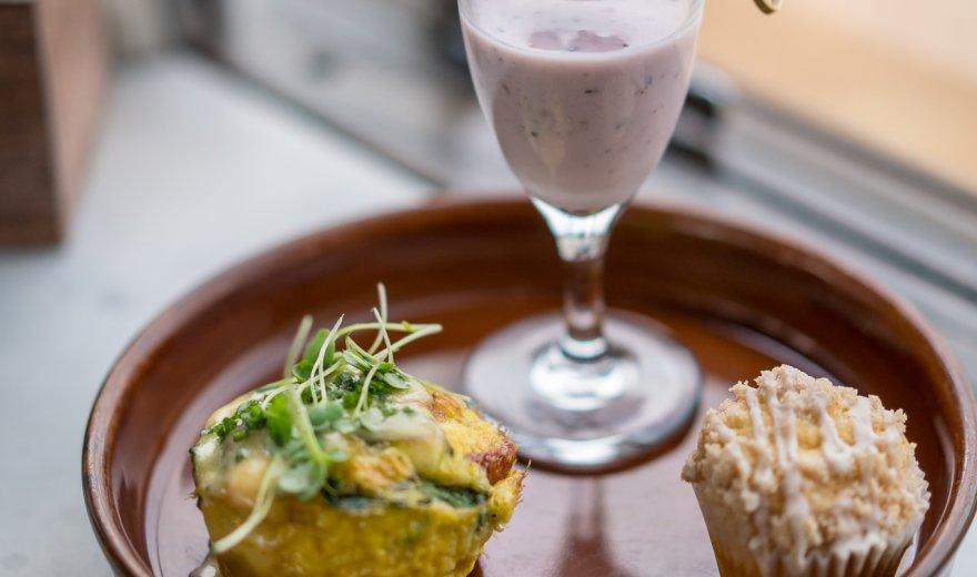 Yogurt parfait, quiche and muffin assorted on a brown platter