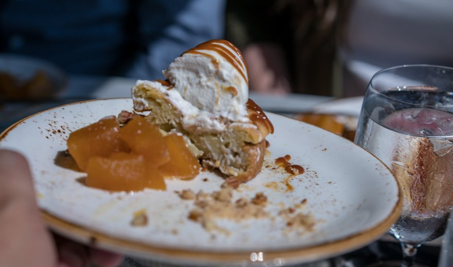 Apple dessert with ice cream and caramel drizzle on a white plate, glass of water in background