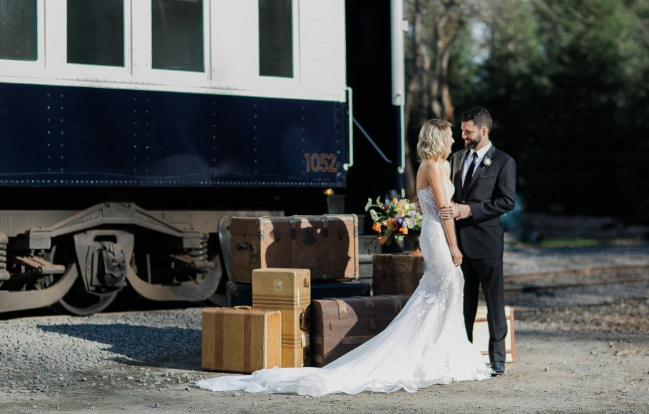 Bride and groom stand outside Napa Valley Wine Train with vintage suitcases