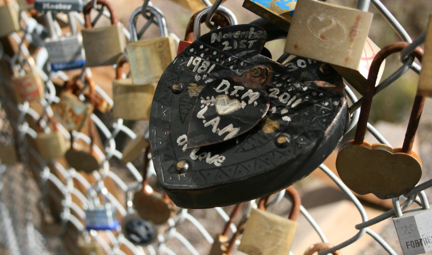 Black padlock with initials written on it attached to fence, other padlocks in background