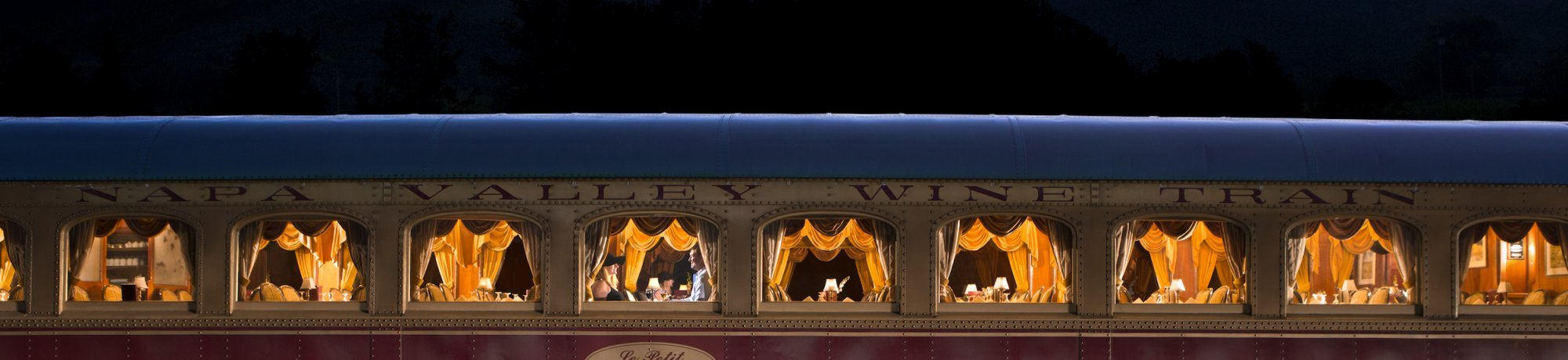 exterior shot of Napa Valley Wine Train le petit gourmet train car with night sky and hill shadows in the distance