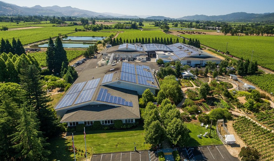Aerial view of Raymond winery modern facilities and lush green vineyards in Napa Valley