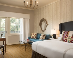 Bedroom at Riverview Terrace Inn with large bed, blue couch, wooden desk and door to balcony