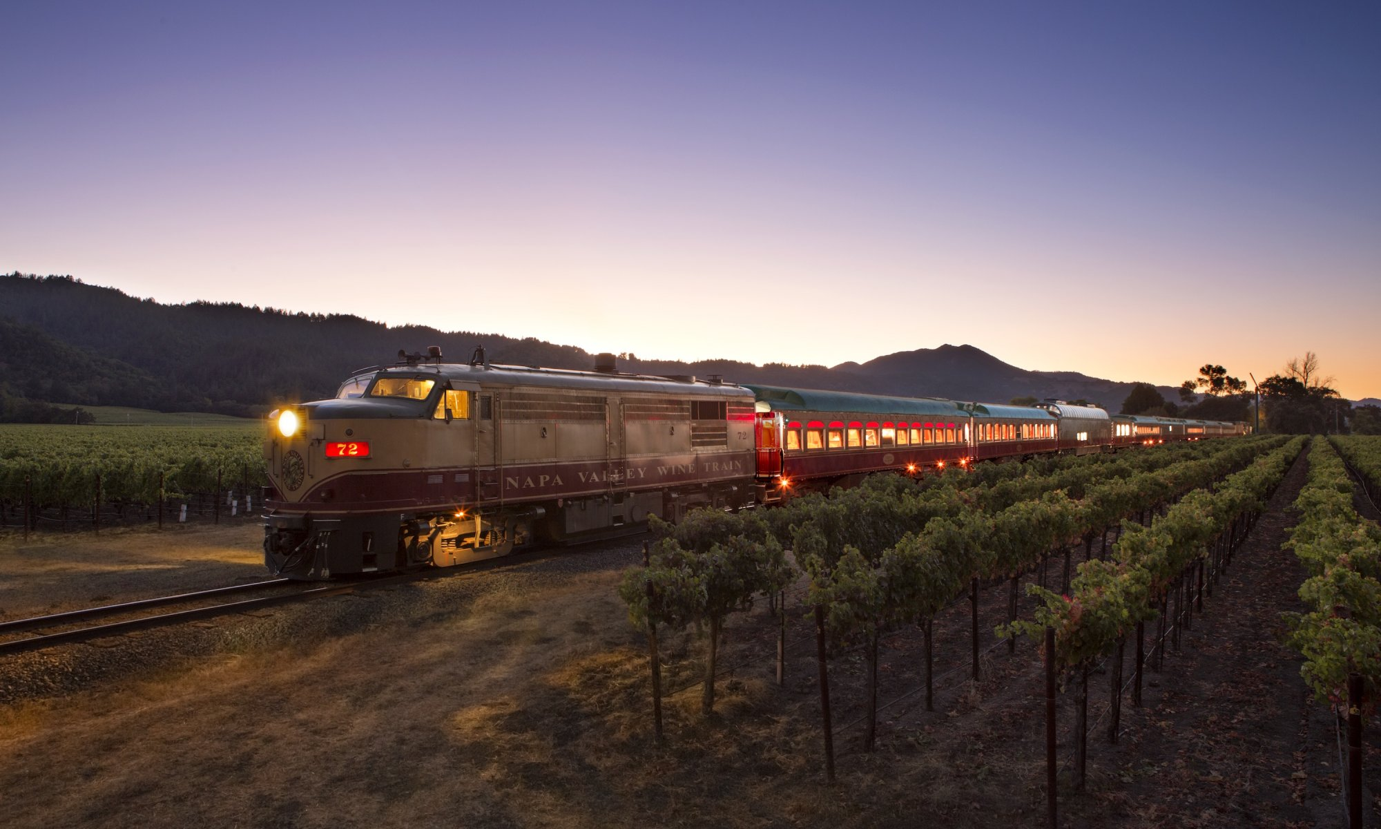 Napa Valley Wine Train travelling through vineyards with sunset in the distance