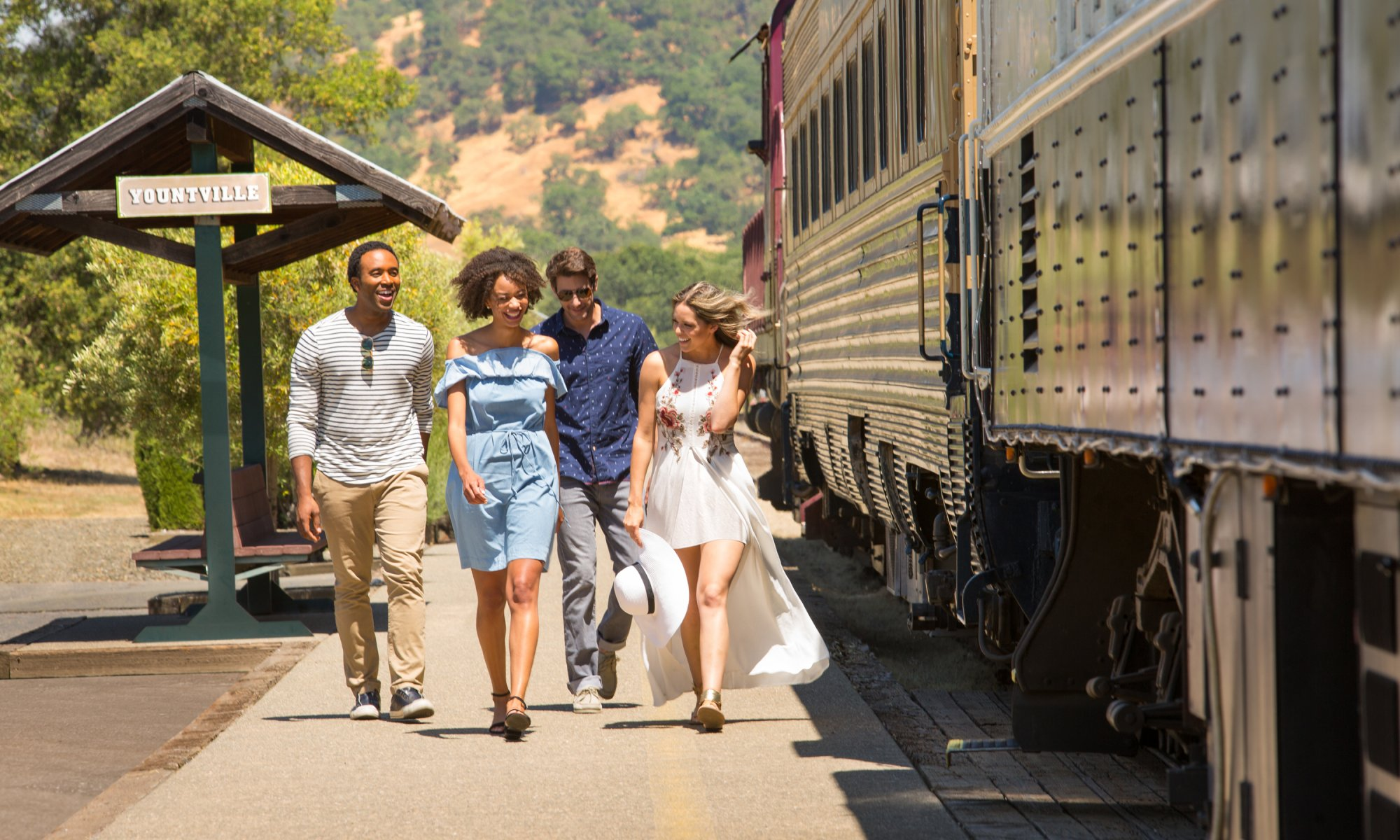4 people laughing and walking beside the Napa Valley Wine Train at the Yountville Station Stop