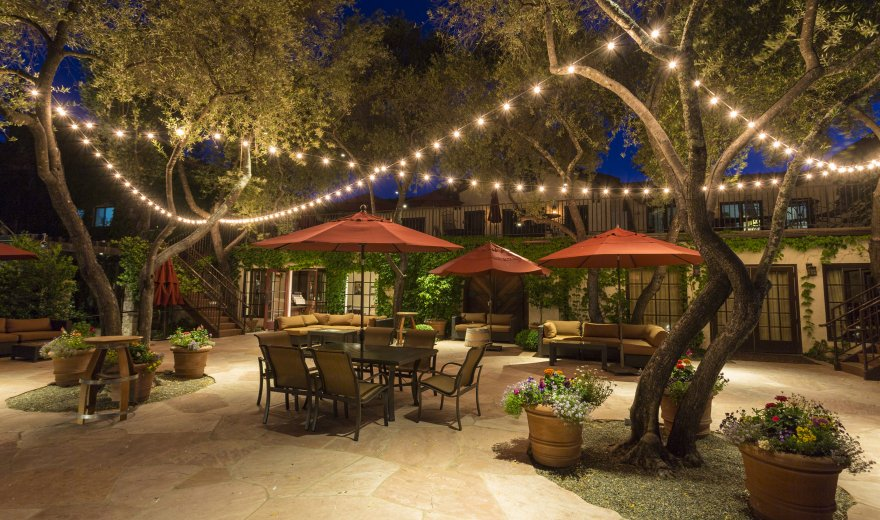 Patio furniture in stone courtyard at dusk, twinkle lights hanging in trees overhead at Grgich Hills Estate in Napa Valley