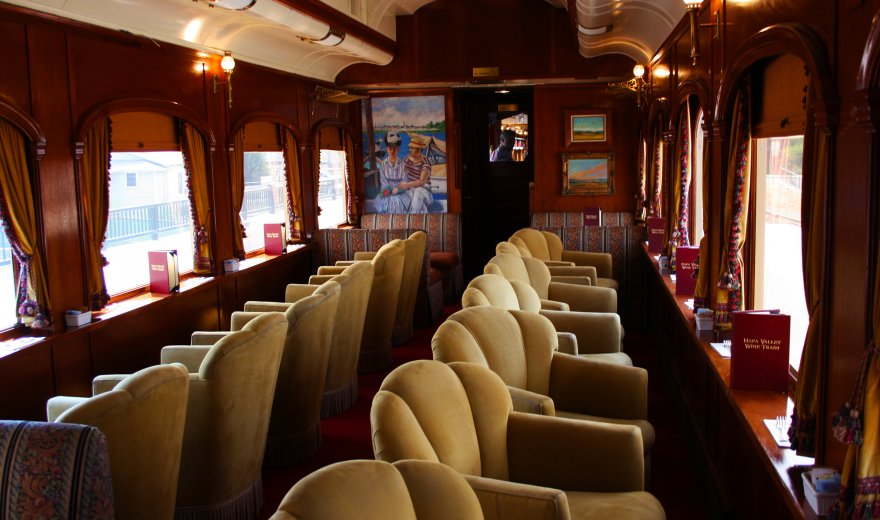 Plush beige velvet chairs lined up in classy wooden railcar on Napa Valley Wine Train