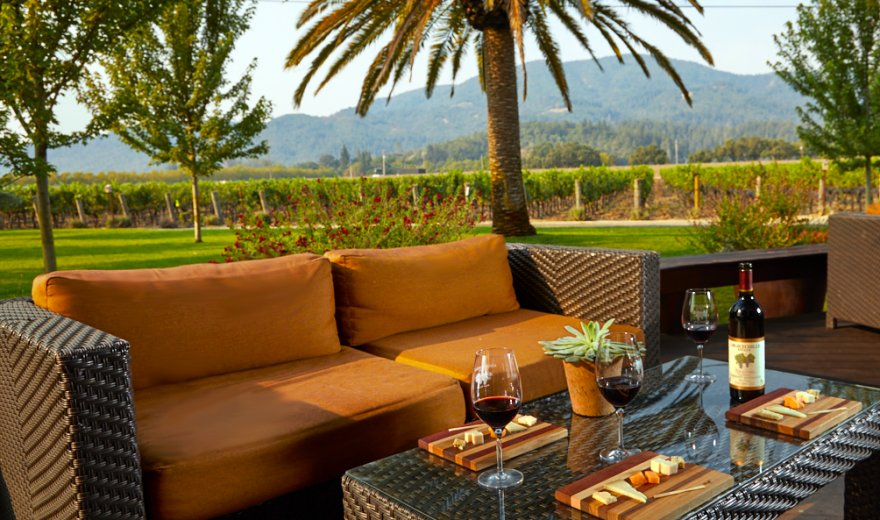 Wicker patio couch and coffee table outside on a sunny day, bottle of wine and cheese boards on table, palm trees and vineyard in background