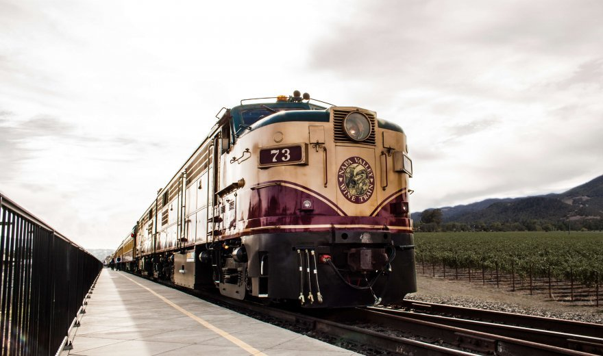 Napa Valley Wine Train's Locomotive 73 travelling by vineyard with grey sky