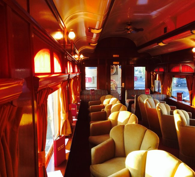 Cabernet Sauvignon train car featuring yellow velvet seats and wood accents