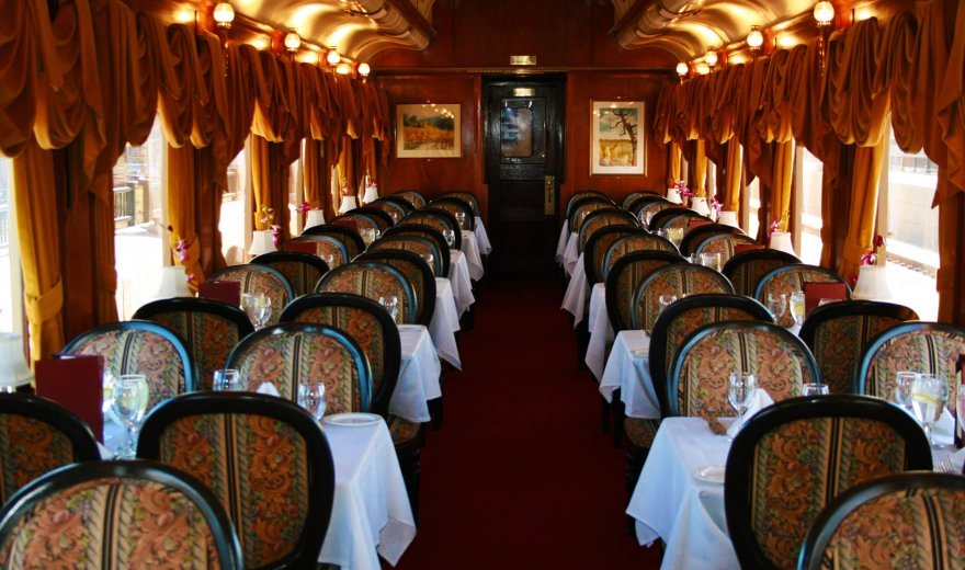 two lines of tables set for dinner with wine glasses on Napa Valley Wine Train's petit gourmet train car