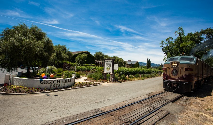 Napa Valley Wine Train pulling up to Grgich Hills Winery where there are balloons outside