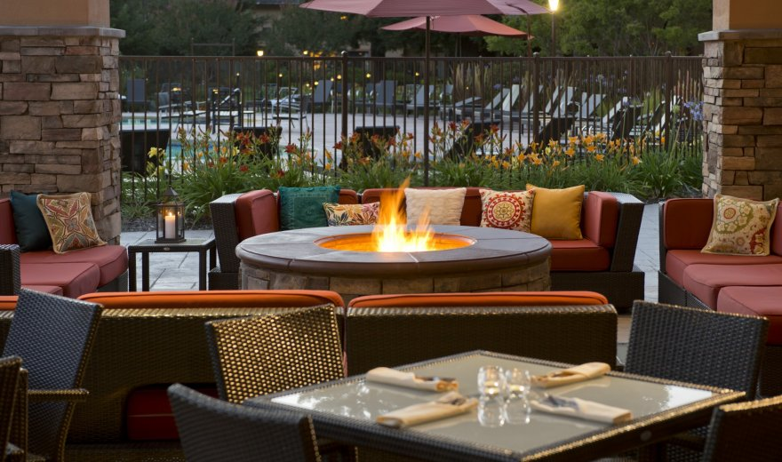 outdoor patio with tables set for a casual dinner, couches, and firepit