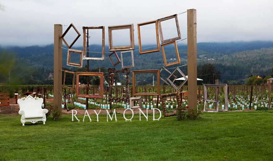 Raymond Vineyard photo booth with multiple frames to stand behind and white chair