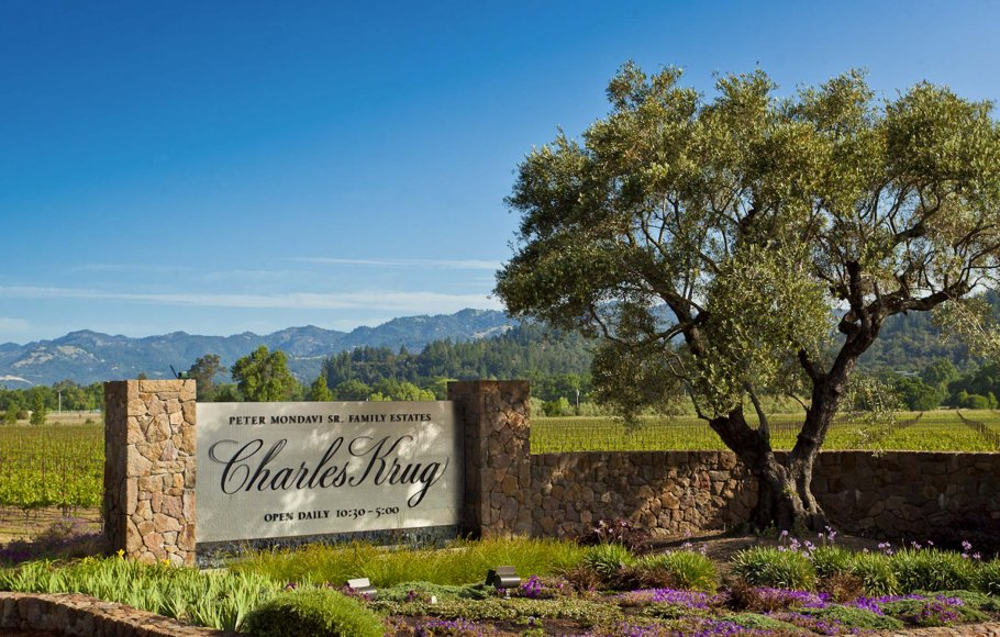 Charles Krug vineyard sign with rows of vines behind and a garden with purple flowers in front