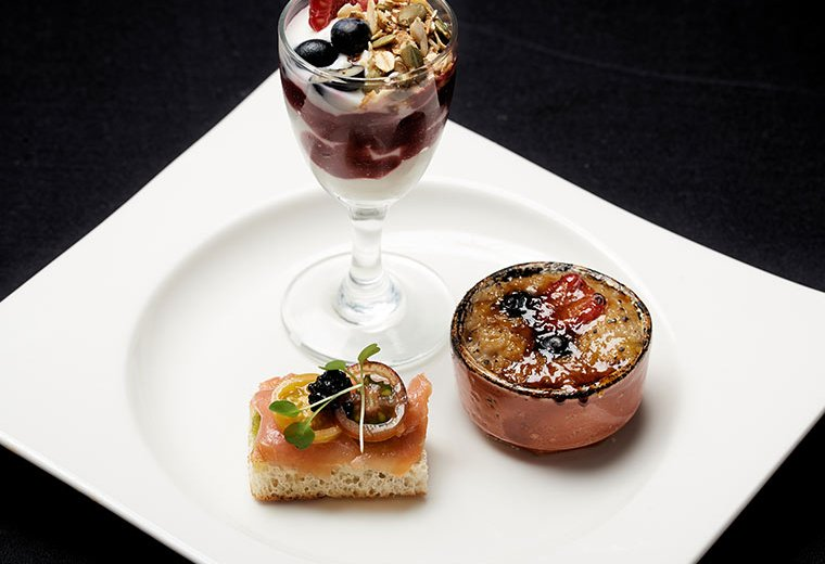 white plate with smoked salmon crostini, yogurt parfait, and savoury breakfast dish