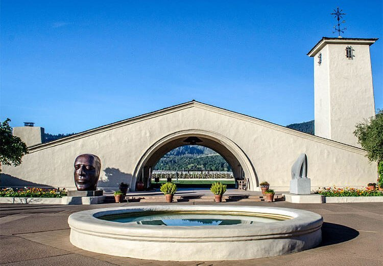 stone archway at Napa Valley winery with sharp edges with garden and a water fountain in front