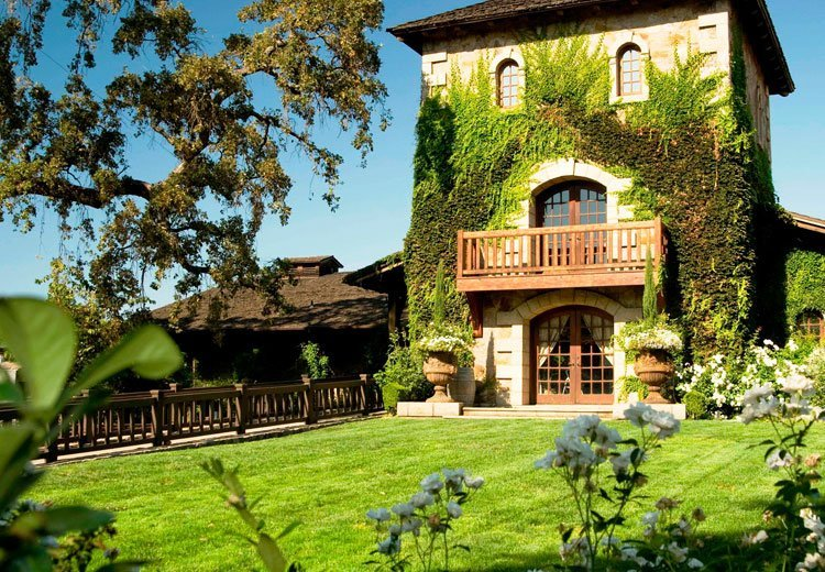 vine-covered exterior of Napa Valley winery with green lawn and white flowers