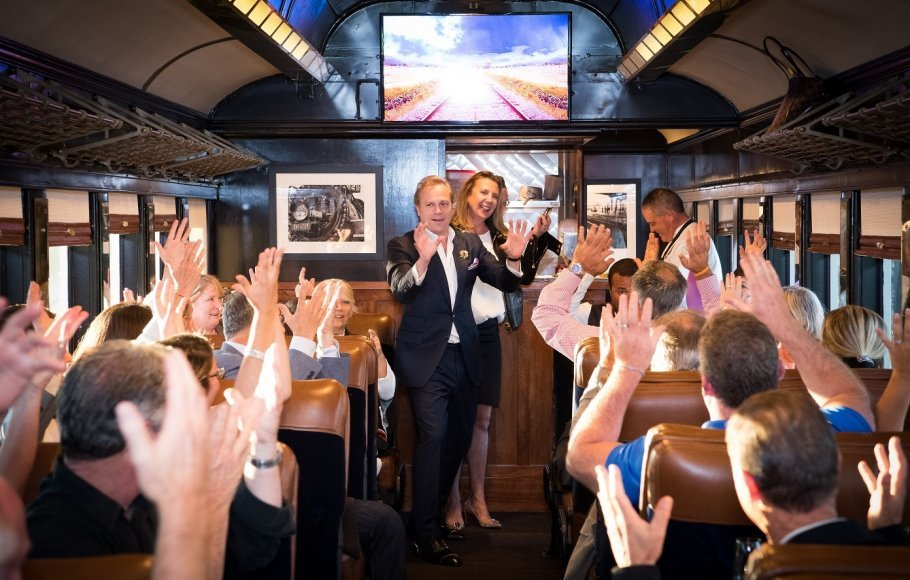 Two people standing up waving on Napa Valley Wine Train as guests sitting down put their hands in the air