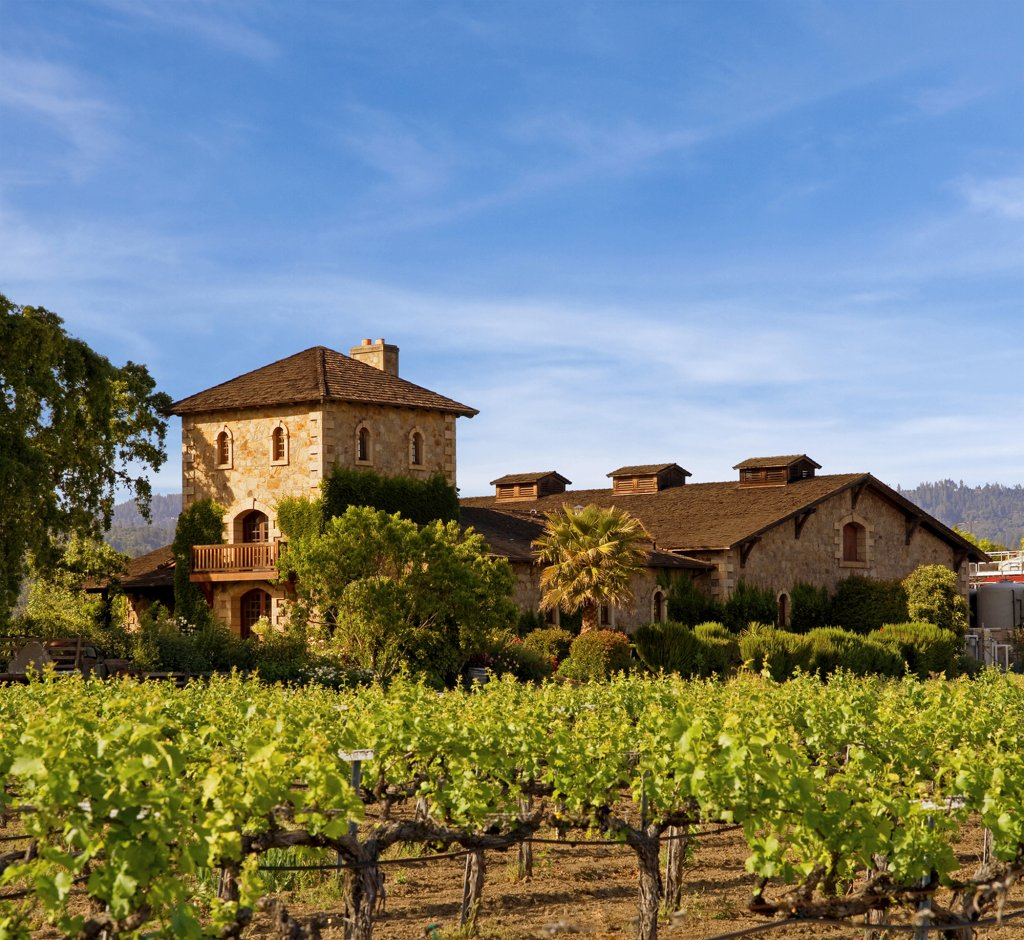 Lush green vineyard in front of brown brick building at V. Sattui Winery in Napa Valley