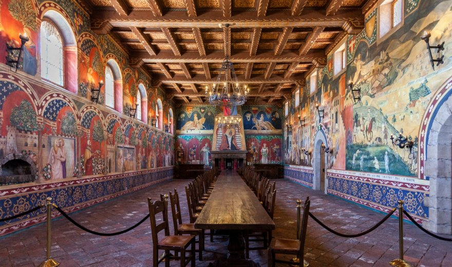 Long wooden table with wooden chairs and brick walls with old murals in Castle Great Hall